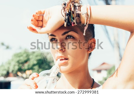 Outdoor summer Portrait of young woman drinking water.  Dark-haired girl at hot summer day - stock photo