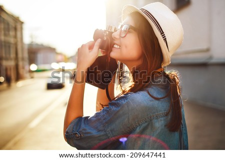 Outdoor summer smiling lifestyle portrait of pretty young woman having fun in the city in Europe in evening with camera travel photo of photographer Making pictures in hipster style glasses and hat  - stock photo