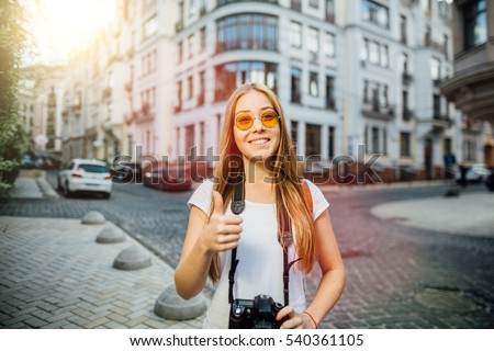 Outdoor summer smiling lifestyle portrait of pretty young woman having fun in the city in Europe in evening with camera travel photo of photographer Making pictures in hipster style sunglasses