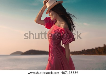 Outdoor summer style woman,sunny fashion portrait of sensual woman wear pink dress on the beach sunset on the ocean seashore.Close-up lifestyle summer outfit of beauty woman,wind hair,wear hat - stock photo