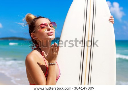 Outdoor summer sunny bikini fashion smiling portrait of pretty young blonde girl in sunglasses posing with surf board on the beach on tropic island vacation giving air kiss - stock photo