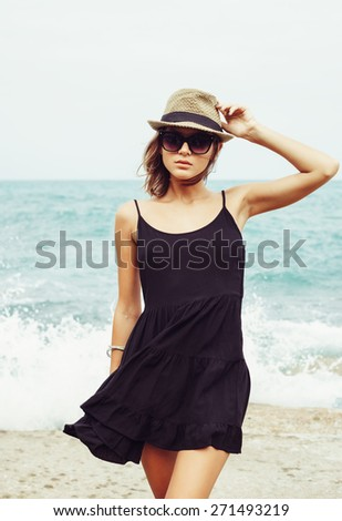 Outdoor summer sunny fashion portrait of pretty young sensual woman posing in sunglasses and black dress on the rocks  on the ocean seashore. Outdoors lifestyle portrait - stock photo