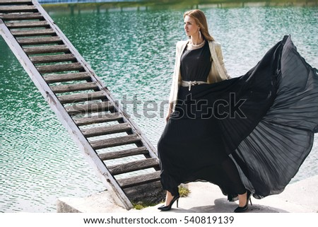 Outdoor sunny fashion portrait of pretty young sensual woman posing in black dress by the lake