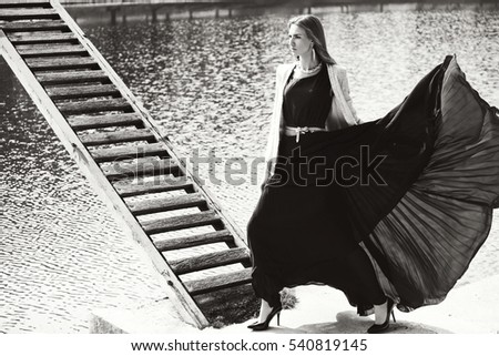 Outdoor sunny fashion portrait of pretty young sensual woman posing in black dress by the lake. black and white