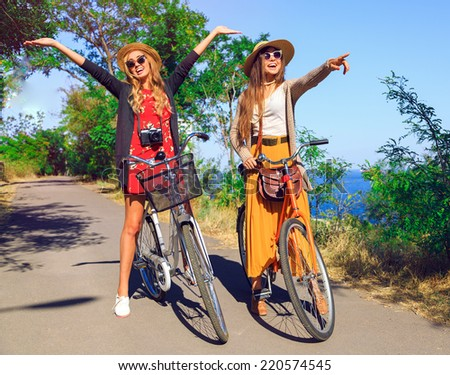 Outdoor sunny fashion portrait of two pretty funny girls, having fun together and going crazy, riding vintage hipster bikes, waring vintage clothes hats and sunglasses. Positive mood. - stock photo