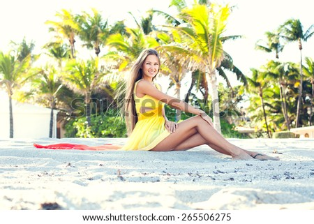 outdoor sunny picture of a beautiful sexy girl in her amazing dress walking down the beach at her summer vacation - stock photo