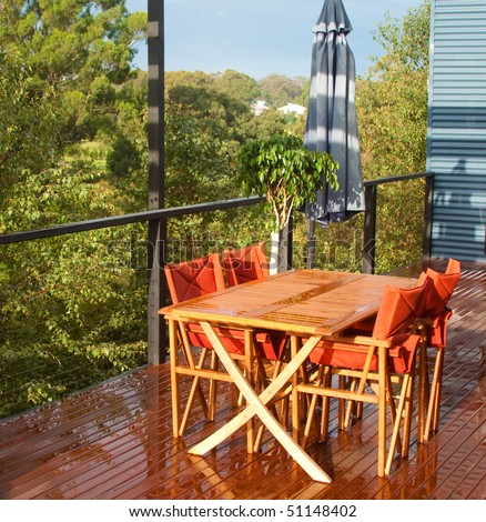 Outdoor table and chairs on a leafy deck after rain.