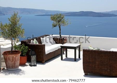Outdoor table and sofas on terrace overlooking sea, Oia Village, Santorini, Cyclades, Greece. - stock photo