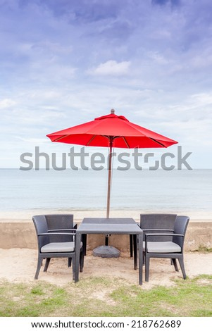 Outdoor table set, beach chairs and red umbrella with beautiful beach and blue sky background. Concept for rest, relaxation, holiday, spa, resort. - stock photo