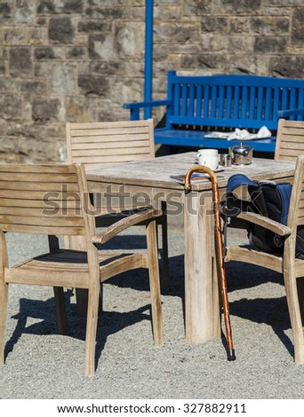 Outdoor table set with  silver teapot, milk jug ,teacups,  map, rucksack, and walking cane.