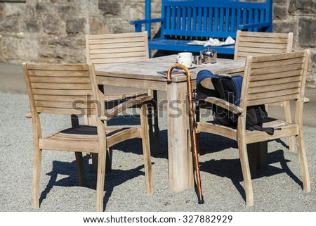 Outdoor table set with  silver teapot, milk jug ,teacups,  map, rucksack, and walking cane. - stock photo