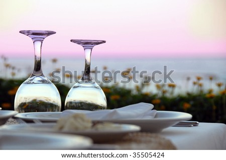 outdoor table with wine glasses over magenta sky - stock photo