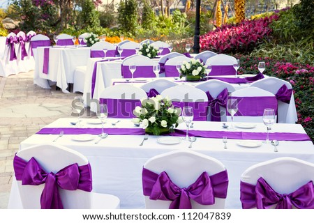 outdoor tables with served plates and wine glasses in the garden - stock photo