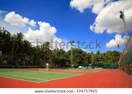Outdoor tennis courts against blue sky and white cloud - stock photo