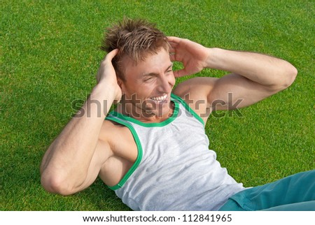 Outdoor training. Young man doing sit-ups on green grass.
