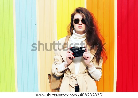 Outdoor trendy stylish portrait of pretty young hipster woman having fun in the city with retro camera, posing in bright colored wall. Photographer making pictures. The style of the '70s  - stock photo