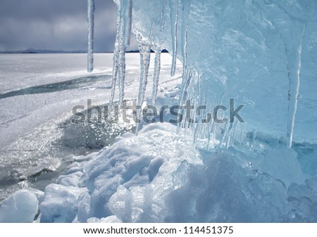 outdoor view of frozen baikal lake in winter with icicles on foreground - stock photo