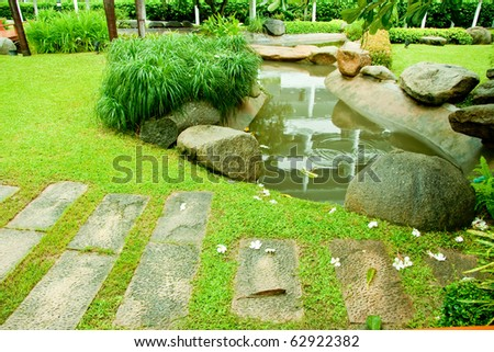 Outdoor walkway among it's raining in the green garden with a small pond. - stock photo