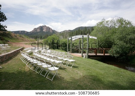 Outdoor wedding ceremony with clouds and mountains - stock photo
