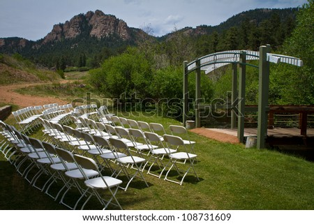 Outdoor wedding ceremony with mountains in background - stock photo
