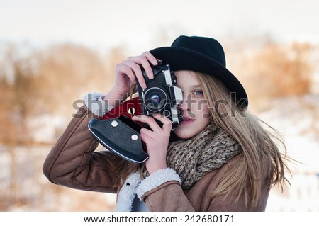 Outdoor winter lifestyle portrait of pretty blonde woman with retro camera - stock photo