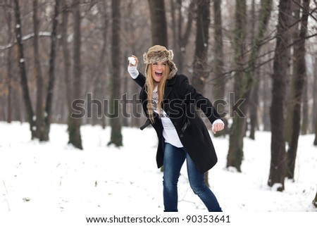 Outdoor winter portrait of a beautiful happy blond young woman in a snowball fight in the woods. She is smiling, wearing a winter hat, and holding a snowball. Very shallow depth of field. - stock photo