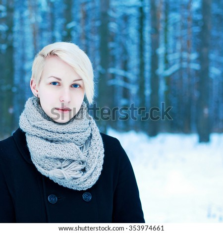 Outdoor winter portrait of blonde happy woman posing in cold blue forest