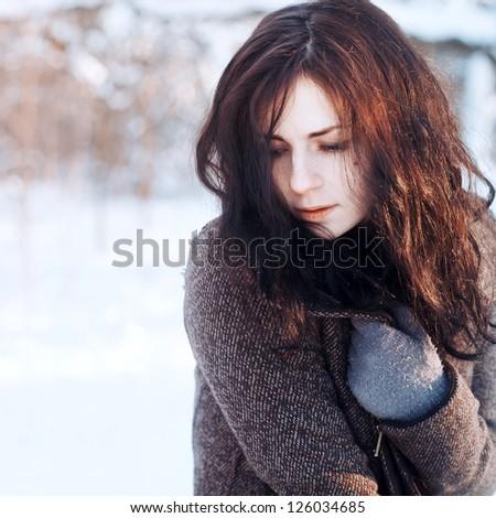 Outdoor winter portrait of young woman dressed in warm woolen coat - stock photo