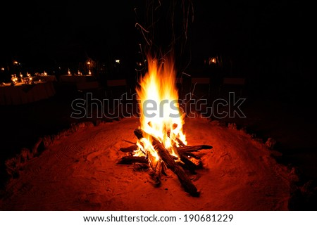 Outdoor wood campfire burning brightly during the darkness of nighttime - stock photo