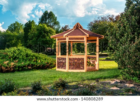 Outdoor wooden gazebo over summer landscape background - stock photo