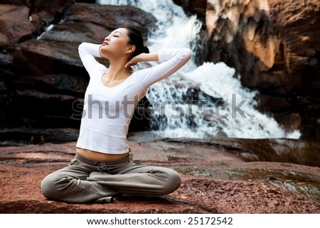 outdoor young woman sitting by the waterfall meditating