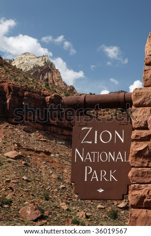 Outdoor Zion National Park sign and mountain landscape