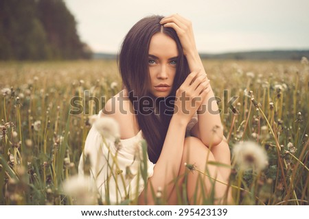 Outdoors art photo of beautiful lady in dandelions field - stock photo