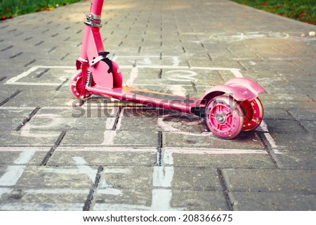 outdoors background of playground with pink little kid scooter and hopscotch - stock photo