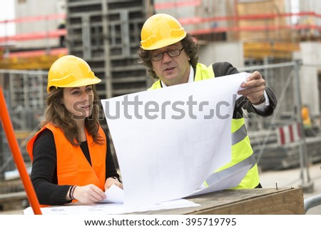 Outdoors. Building engineer and architect reviewing blueprints - stock photo