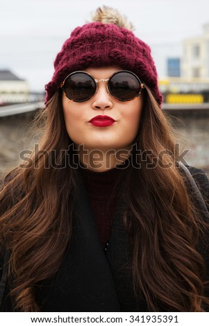 Outdoors close up portrait young sexy brunette woman in round sunglasses, smiling and  posing on a city street. Perfect skin facial make-up. Wearing a fashionable coat, burgundy dress and hat