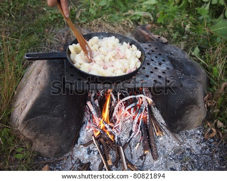 Outdoors cooked stew boiling on the fire - stock photo