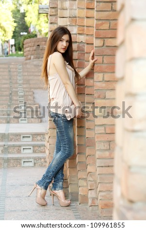 Outdoors fashion portrait of beautiful young brunette girl - stock photo