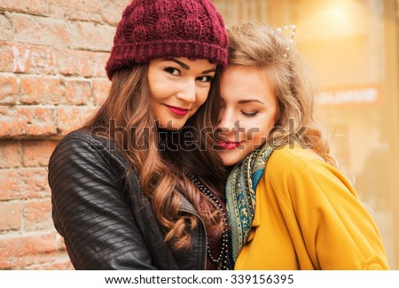 Outdoors fashion portrait young pretty best girls friends in friendly hug. Walking at the city. Posing at the street. Wearing stylish outerwear and hats. Bright make up. Positive emotions. Cuties - stock photo