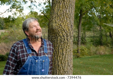 outdoors guy in plaid shirt & dungarees checks the weather