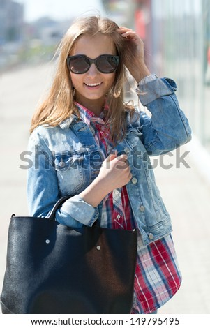 Outdoors headshot of a beautiful young woman walking down the street carrying a her hand bag - stock photo