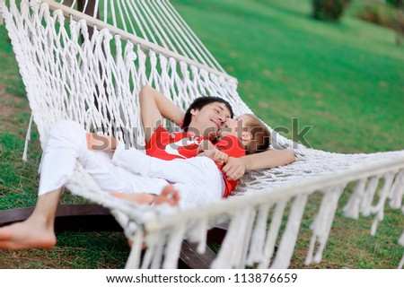 outdoors in a white hammock resting father and son in red shirts - stock photo