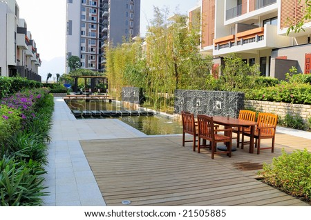 Outdoors landscape with resting chairs and fountain and tree in a new residential district - stock photo