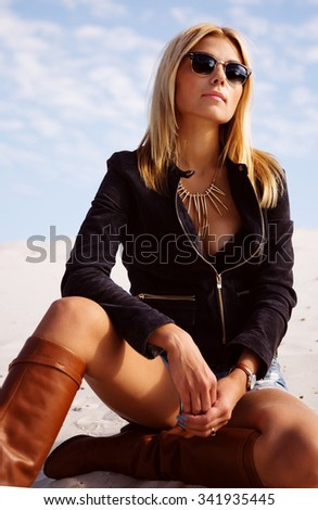 Outdoors lifestyle fashion portrait of young pretty blonde girl, wearing stylish suede jacket, high beige leather boots and sunglasses. Sitting on the sand, basking in the sun. Romantic mood - stock photo