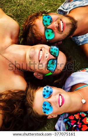 Outdoors lifestyle portrait of company young pretty best friends. Smiling, lying on the grass and looking at the sky. Wearing bright t-shorts and stylish sunglasses. In sunglasses reflected palm trees - stock photo