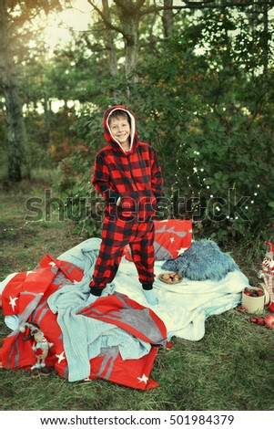 Outdoors Little boy standing in bed in red pajamas with toys and fruit