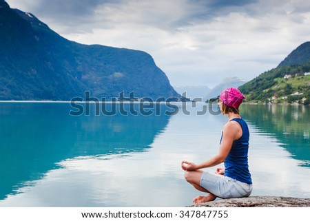 outdoors meditation - relaxed young yoga woman in praying lotus pose,closing eyes to relax and meditate - stock photo