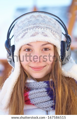Outdoors on a winter day. Woman listening music. - stock photo