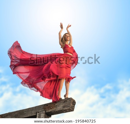 Outdoors portrait of a beautiful girl in airy dress, view from below - stock photo