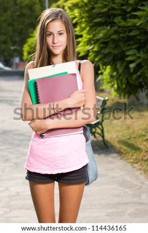 Outdoors portrait of a beautiful tanned teen student girl. - stock photo